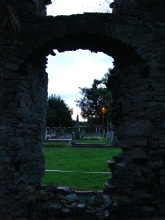 A peep through the window of the ruined church... twilight gloom setting in... no... that's not the glimmering... it's a street light...