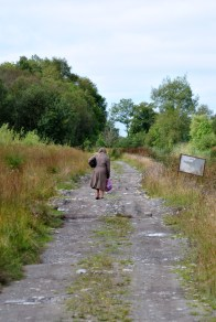 The lady in the brown coat hobbles along the stony towpath