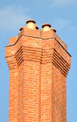 Red brick chimney detail against a blue sky...