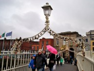 Pink umbrella on Dublin's Ha'penny Bridge. Note the seated beggar... signs of the times? Well... the Irish and Greek flags as twins should be a rather good indication....