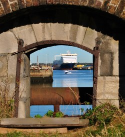 Window into a view of the past and the now... a glimpse through old stone wall at a ferry and speed boat in Dublin's harbour area...