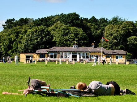 Did they drop from the sky? Seems a tad surreal... two sleeping cyclists against the backdrop of a cricket game...