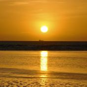 Winter sunrise out over Dublin Bay, Ireland... silhouetting the ship on the horizon...
