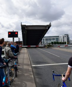The cyclists have to wait while the bridge lifts...