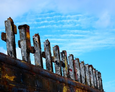 The ribs of the old boat... pointing upward... against the cloud patterns...