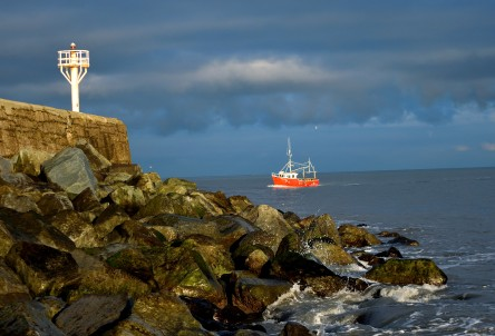 The Arklow South Pier is well lit up by the low winter sun... and the boat is running for the harbour mouth...