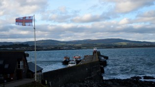 Chilly... as driven by the stiff wind right off the Irish Sea... Wicklow Harbour's East Pier with RNLI flag...